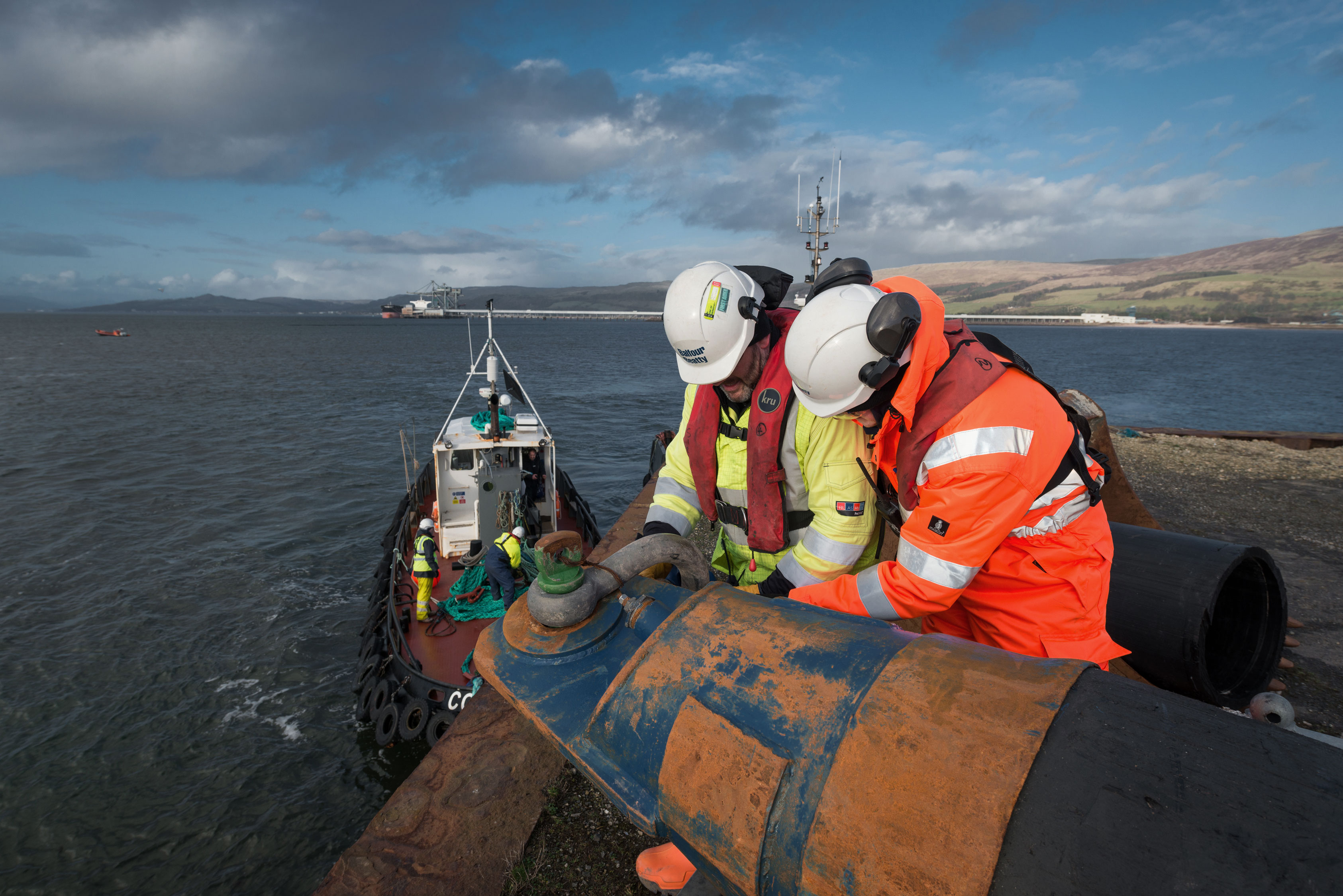Men in hard hats working on laying pipes by sea, hunterston, scotland