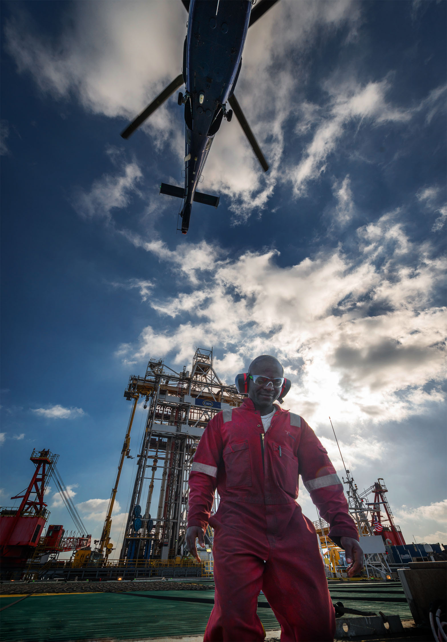 Man in red fire suit on oil rig with helicopter taking off