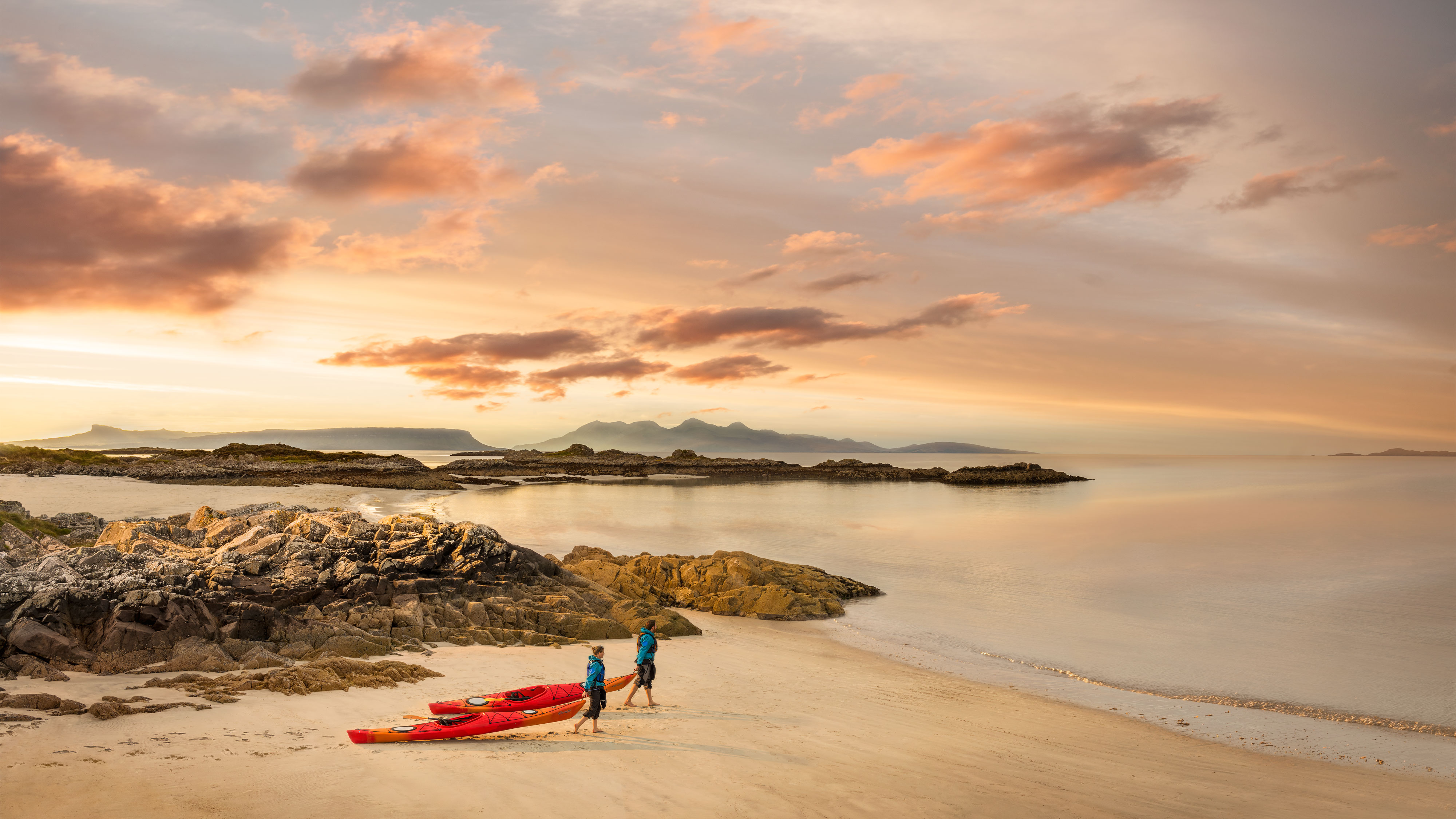 Couple pulling red canoes across sandy beach in Scotland at sunset