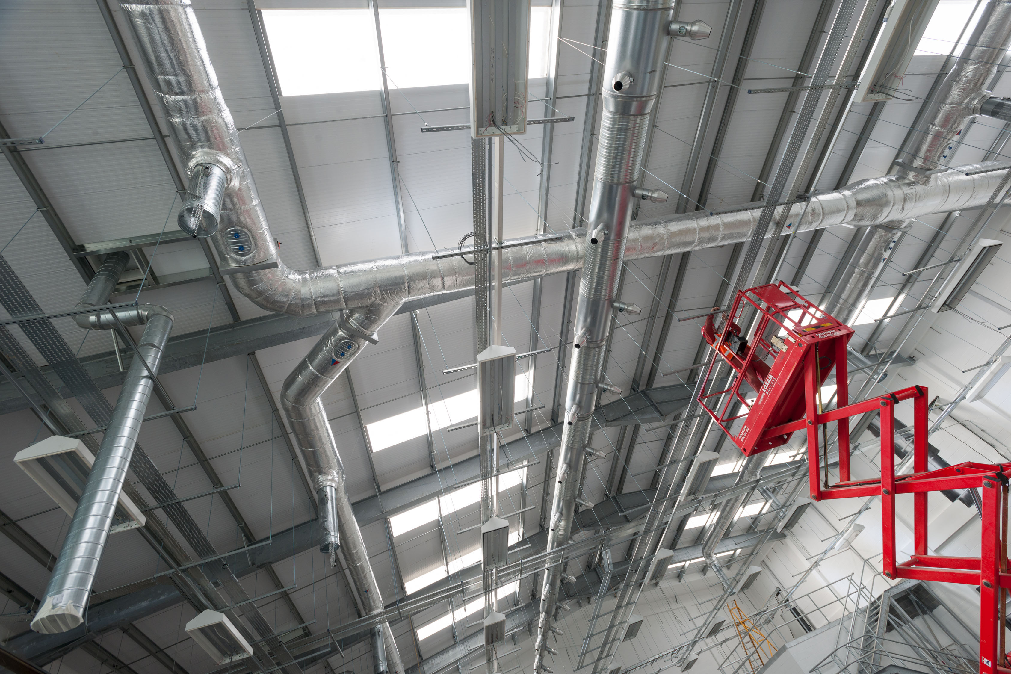 Man on red scaffolding tower fixing roof interior of silver grey industrial unit