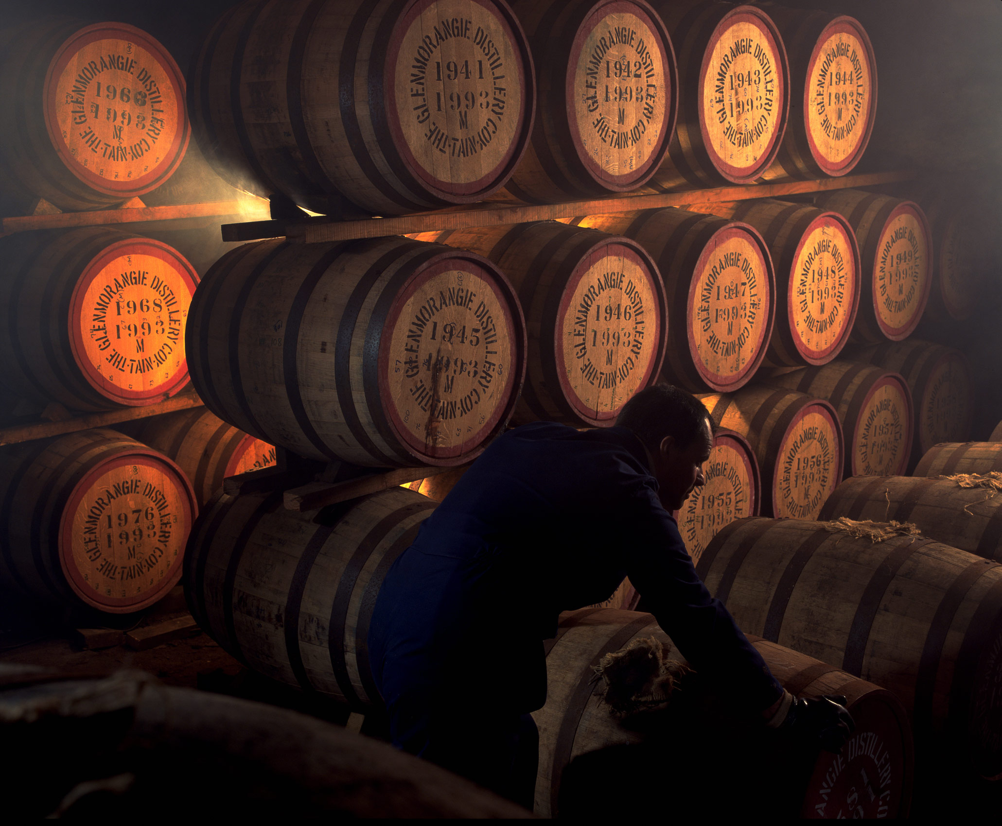 Man rolling barrels in Glenmorangie Whisky distillery,  Scotland