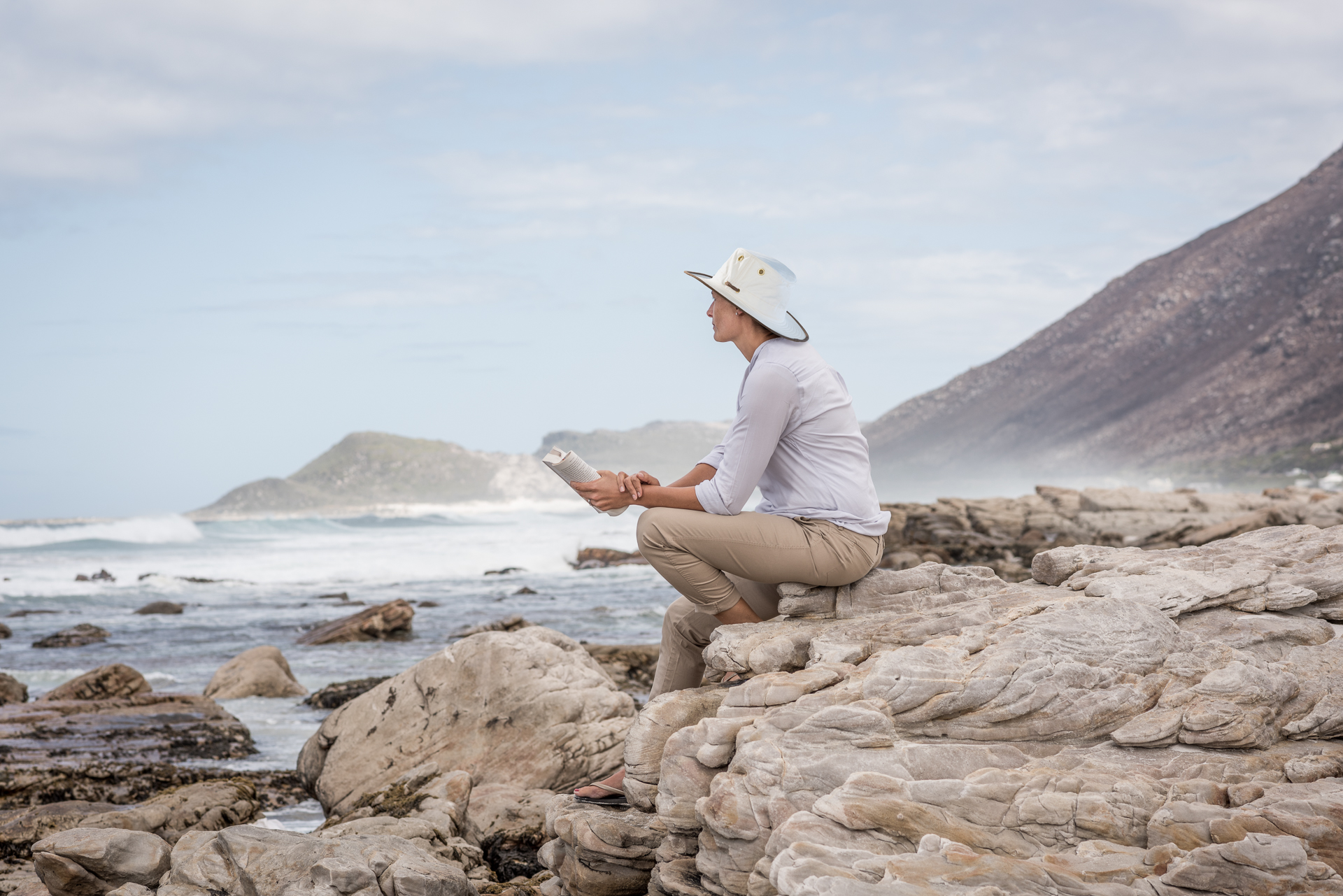 Girl with book sitting on rocks and looking out to sea in South Africa