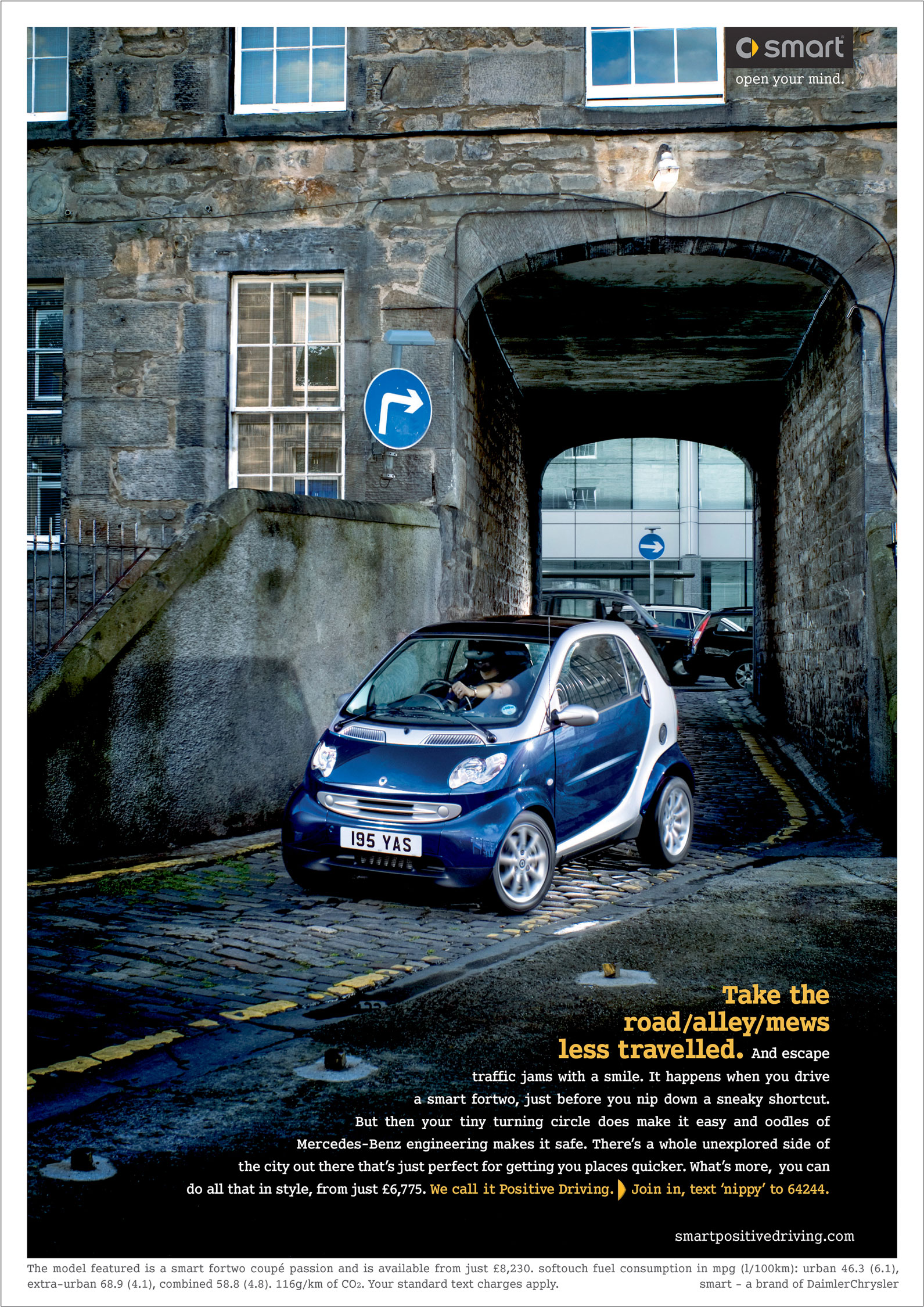 Blue Smart car driving down narrow alley in edinburgh scotland