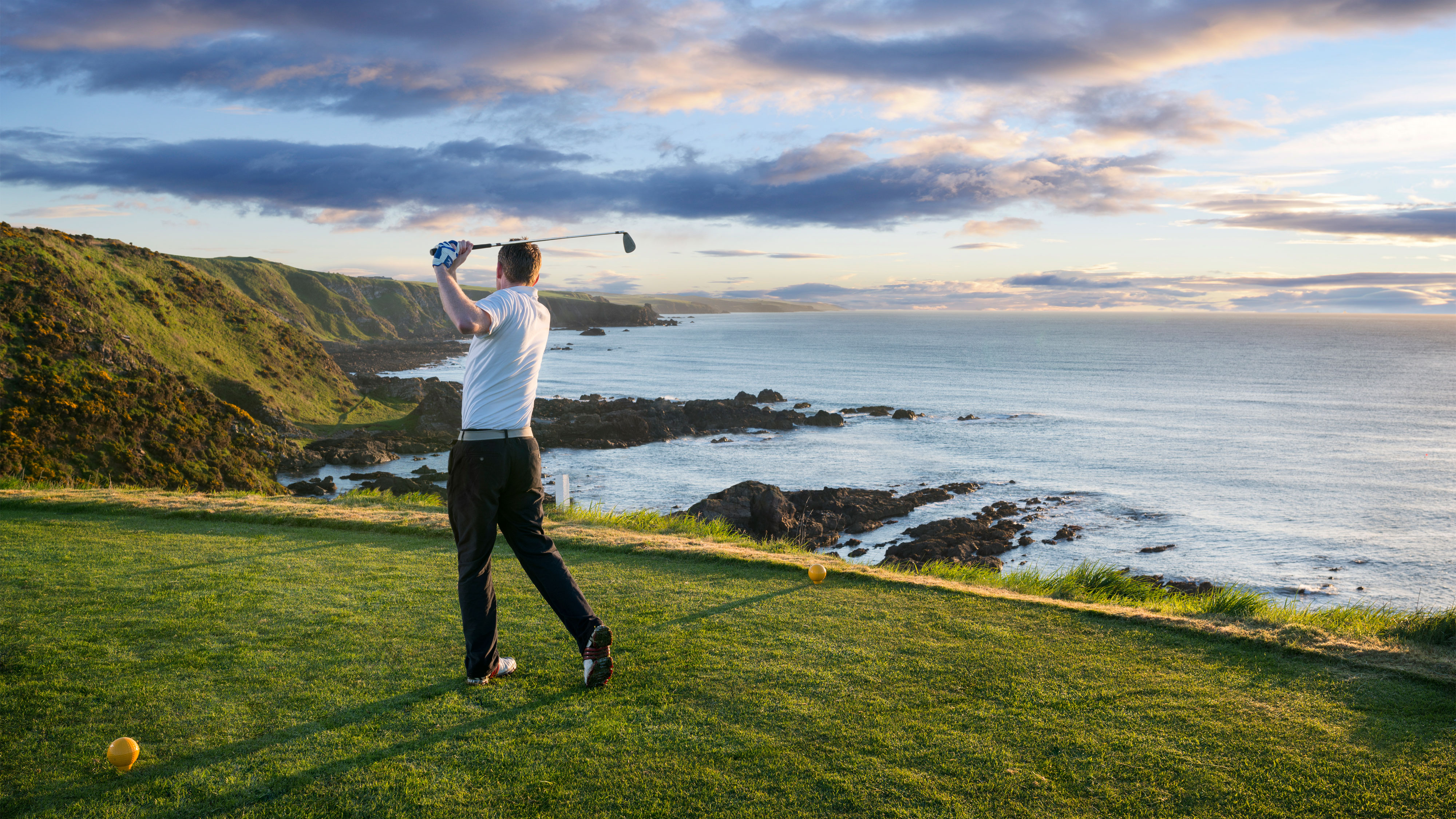 Golfer teeing off by cliffs and sea at Stonehaven scotland